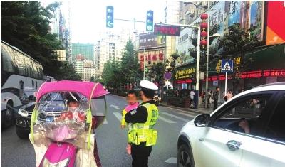 2岁女童街头迷路 交警抱怀中指挥交通