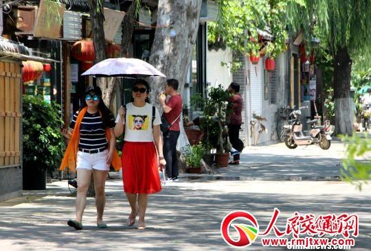 图为,济南街头,市民墨镜、阳伞全副武装出行。 赵晓 摄